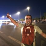 A man covered with blood points at the Bosphorus bridge as Turkish military clashes with people at the entrance to the bridge in Istanbul on July 16, 2016.  Turkish military forces on July 16 opened fire on crowds gathered in Istanbul following a coup attempt, causing casualties, an AFP photographer said. The soldiers opened fire on grounds around the first bridge across the Bosphorus dividing Europe and Asia, said the photographer, who saw wounded people being taken to ambulances.   / AFP / Bulent KILIC        (Photo credit should read BULENT KILIC/AFP/Getty Images)
