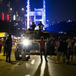 People take over a tank near the Fatih Sultan Mehmet bridge during clashes with military forces in Istanbul on July 16, 2016.  Istanbul's bridges across the Bosphorus, the strait separating the European and Asian sides of the city, have been closed to traffic. Turkish military forces on July 16 opened fire on crowds gathered in Istanbul following a coup attempt, causing casualties, an AFP photographer said. The soldiers opened fire on grounds around the first bridge across the Bosphorus dividing Europe and Asia, said the photographer, who saw wounded people being taken to ambulances.  / AFP PHOTO / GURCAN OZTURKGURCAN OZTURK/AFP/Getty Images
